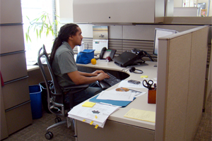 Communications professional works at cubicle in Friends Center's open-plan office space.