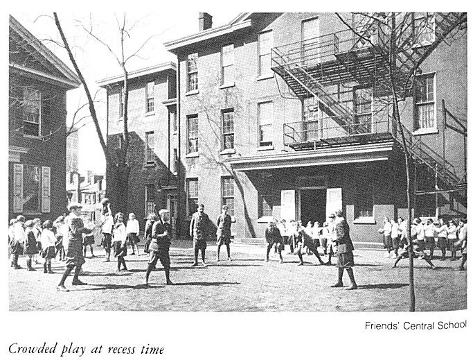 Historic image of children playing in the courtyard at Friends Center, with the Meetinghouse and 1520 Race Street building in the background. The boys are wearing knickers and caps.